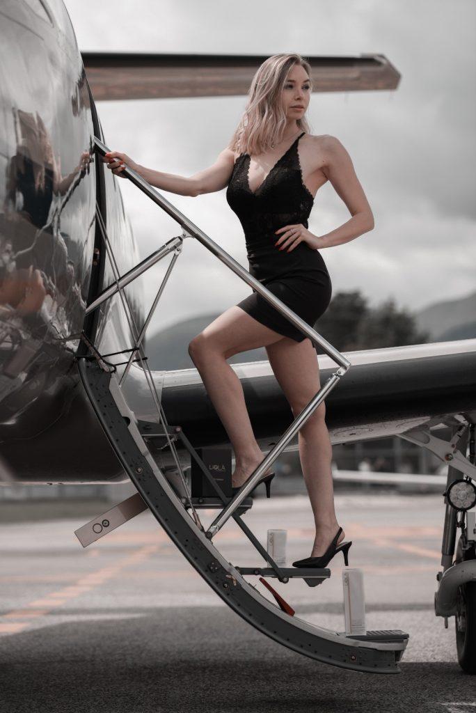 Modella che sale su jet privato con la linea time control