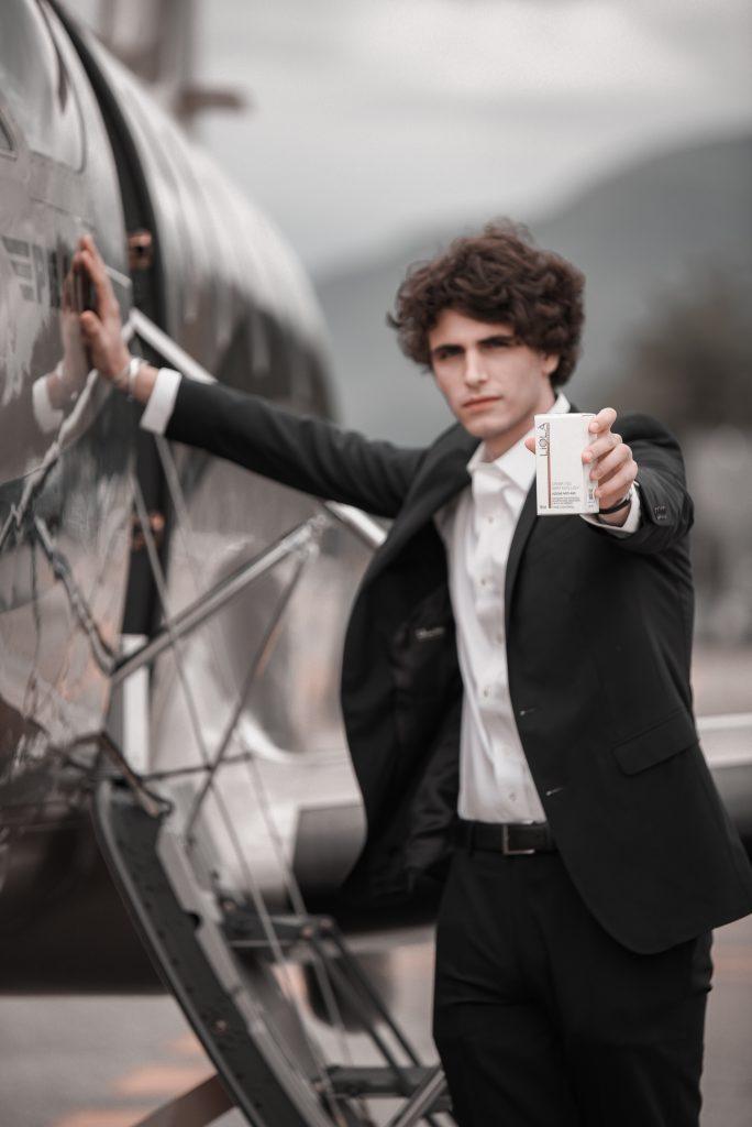 Modello che tiene in mano crema viso linea time control Liolà Cosmetics su jet privato