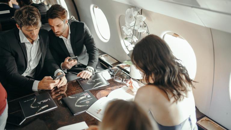 Persone su jet privato che tengono in mano brochure e prodotti Liolà Cosmetics